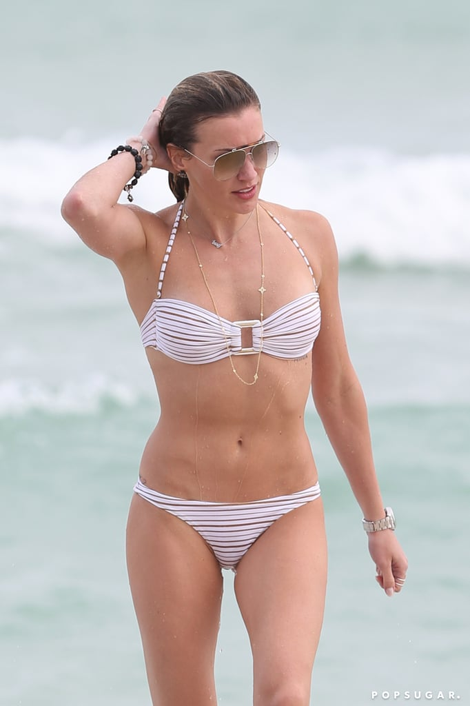 "Judging from these photos of Katie Cassidy's latest trip to the beach, adhering to a superhero fitness regimen certainly has its perks. The Arrow actress headed to her favorite vacation spot in Miami on Monday to splash around in the surf, goof off with friend Tommy Cole, and nearly shut down all of Florida with a deadly heat wave, thanks to her bangin' bikini body. You know, the usual. She laughed her way up and down the sand in a black-and-brown Acacia two-piece, which showed off what appears to be a new tattoo on her hip that reads, ""Just Breathe."" Throughout the week, the actress returned to the beach, where she flaunted her killer physique in a barely there orange bikini, a black-and-white bathing suit with cool cutouts, and a white striped two-piece. Keep scrolling to see more pictures of the star, and then check out some sexy snaps from her Christmas vacation last year!"