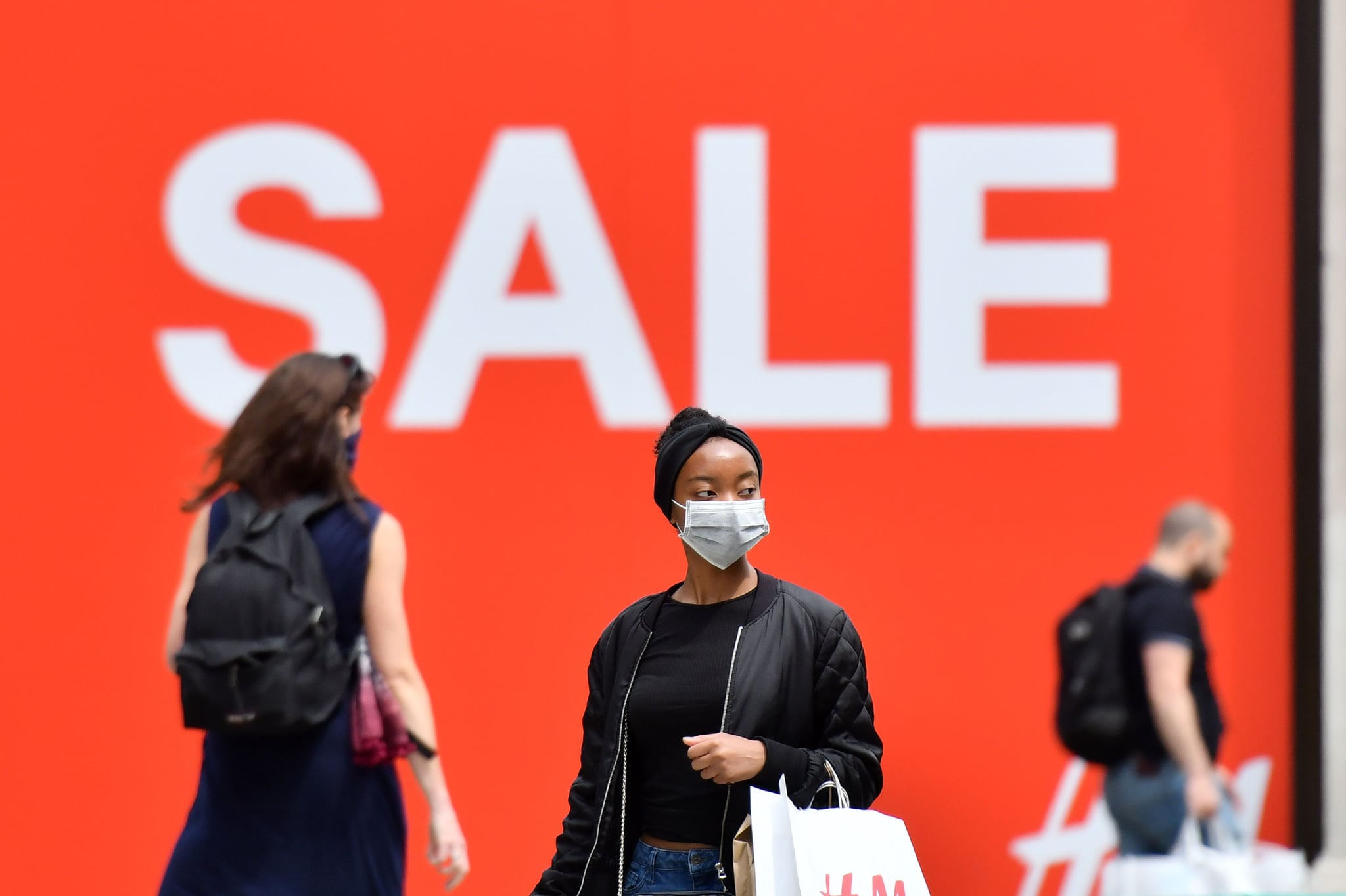 A shopper wears a mask as a precaution against the transmission of the novel coronavirus as she walks past a sale sign in shop window on Oxford Street in London on July 14, 2020. - Face masks will be compulsory in shops and supermarkets in England from next week, the government said on July 14, in a U-turn on previous policy. (Photo by JUSTIN TALLIS / AFP) (Photo by JUSTIN TALLIS/AFP via Getty Images)
