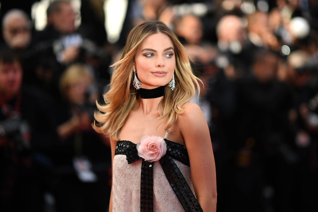 Margot Robbie legitimately looked like the coolest person at the Once Upon a Time in Hollywood premiere — and Brad Pitt and Leonardo DiCaprio were there! For the red carpet event during the 2019 Cannes Film Festival on May 21, the actress wore sequin Chanel pants and a matching top with a big bow and rose accent. She completed the daring outfit with satin mule heels, a thick black choker, and art deco earrings. Though a quintessential example of Chanel's ladylike aesthetic, the retro-feeling outfit is also fitting considering the Quentin Tarantino film takes place in 1969, with Margot portraying the late actress Sharon Tate. Ahead, see photos of the red carpet look that will likely go on to be one of Margot's more memorable ones.       Related:                                                                                                           The Cannes Red Carpet Is Off to Quite the Stylish Start