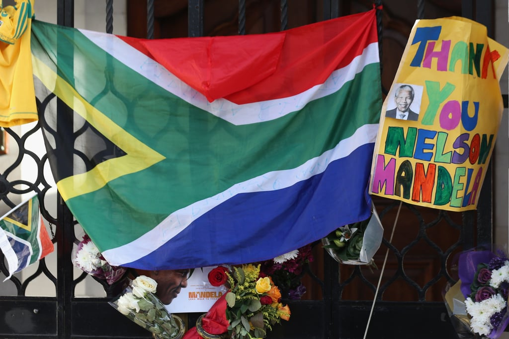 Flags, flowers, and signs honored Nelson Mandela outside London's South African embassy.