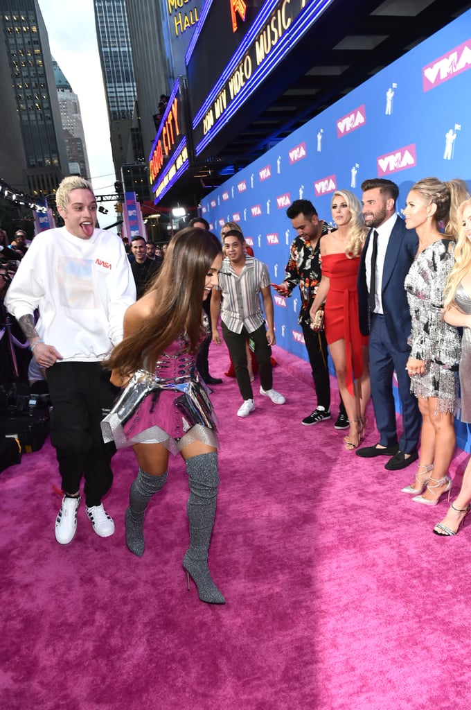 """Ah, to be young and in love. On Aug. 20, Ariana Grande and Pete Davidson attended the 2018 MTV Video Music Awards for their first red carpet appearance as an engaged couple. While the two stopped to take several sweet pictures, Ariana and Pete were photographed fleeing from the red carpet soon after — interrupting a shot of The Hills cast reunion in the process! Why did Ariana and Pete leave in such a hurry? While the 25-year-old pop star is performing her latest single """"God Is a Woman,"""" she wasn't set to open the award show. Once inside, Ariana and Pete slowed down their mad dash to take more pictures while looking lovingly into each other's eyes. And just like that, all was right again.       Related:                                                                                                           Pete Davidson's in Sweats, but Ariana Grande's VMAs Look Is Working Overtime"""