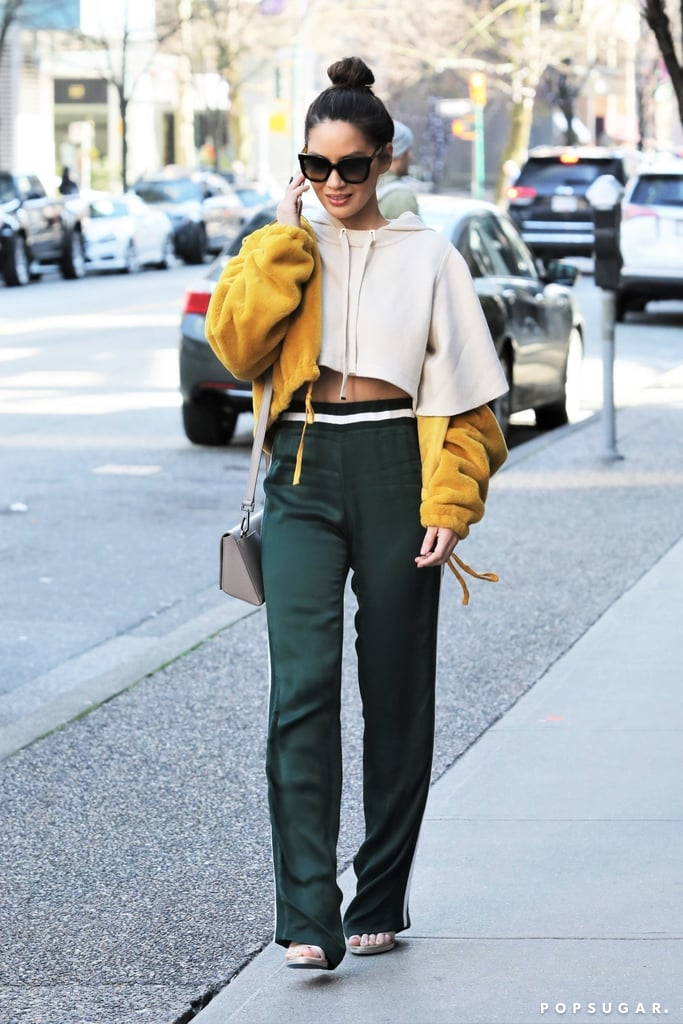 Some women like to go matchy-matchy with their sweatsuits, while others mix it up. So if you're wondering how, exactly, to style your cropped hoodie and track pants, let Olivia Munn show you. The actress threw together a laid-back ensemble that was casually stylish for Los Angeles. She wore a beige, slashed hoodie with emerald track pants (note the black-and-white stripe details), while a fluffy yellow coat worn off the shoulders gave her outfit a bright pop of color. Instead of sneakers, Olivia kept it semifancy with a pair of heels. Accessories such as a crossbody bag and Rag & Bone sunglasses locked in the cute outfit. The look, for sure, isn't hard to re-create, because all you need are the right pieces. And you can amp up your wardrobe with Olivia's $265 sporty hoodie from Ba&sh. The voluminous sleeved number can be worn with just about anything and is the perfect foundational item. See the star's full outfit ahead, then shop some inspired sweatshirts.       Related:                                                                                                           Olivia Munn's One-Piece Swimsuit Plunges Further Than You Thought Possible