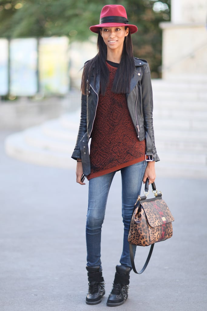 Fall-feeling cool, thanks to a leather jacket, cranberry fedora, and studded sneakers.