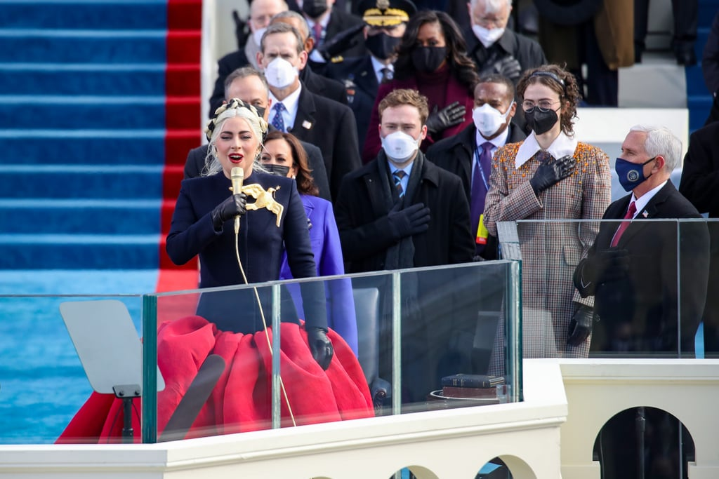 """If you've ever stared at your closet scratching your head wondering what the heck to wear, just imagine if you had to pick out an outfit for President Biden's inauguration. On Jan. 20, Lady Gaga had the great honour of singing the national anthem at the Presidential Inauguration, and she wore the perfect outfit: a custom Schiaparelli Haute Couture ensemble. The look was complete with a red faille skirt and a fitted navy cashmere jacket adorned with a gilded gold dove. It was statement-making, it was head-turning, and it was undeniably patriotic. We did not expect anything less from Gaga! In a statement, the brand's designer Daniel Roseberry spoke about the significance of the avant-garde design. """"As an American living in Paris, this ensemble is a love letter to the country I miss so dearly and to a performer whose artistry I have so long admired. Maison Schiaparelli is honoured to have this chance to dress the iconic Lady Gaga on this historic Inauguration Day. God Bless Lady Gaga and God Bless America,"""" he said. Check out photos of Gaga's stunning outfit ahead, and then see the photos of Vice President Kamala Harris's purple Inauguration Day coat.      Related:                                                                                                           Lady Gaga's Powerful White Cape Coat at Capitol Hill Is a Nod to the Suffragette Movement"""