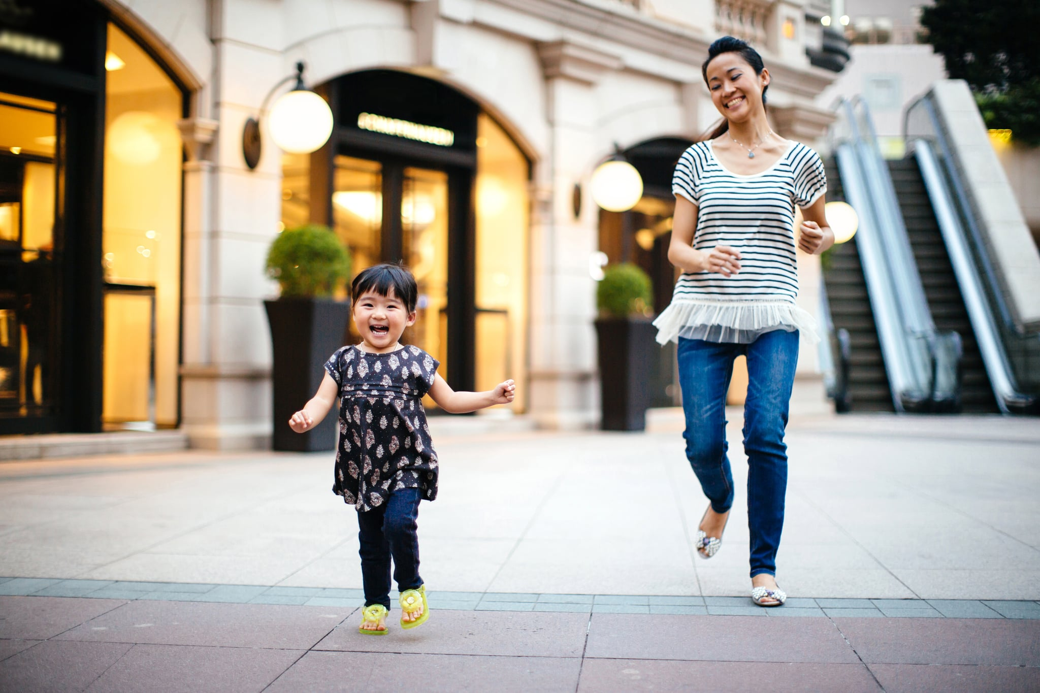 Pretty young mom playing with and chasing after running toddler girl in the square, both smiling joyfully.