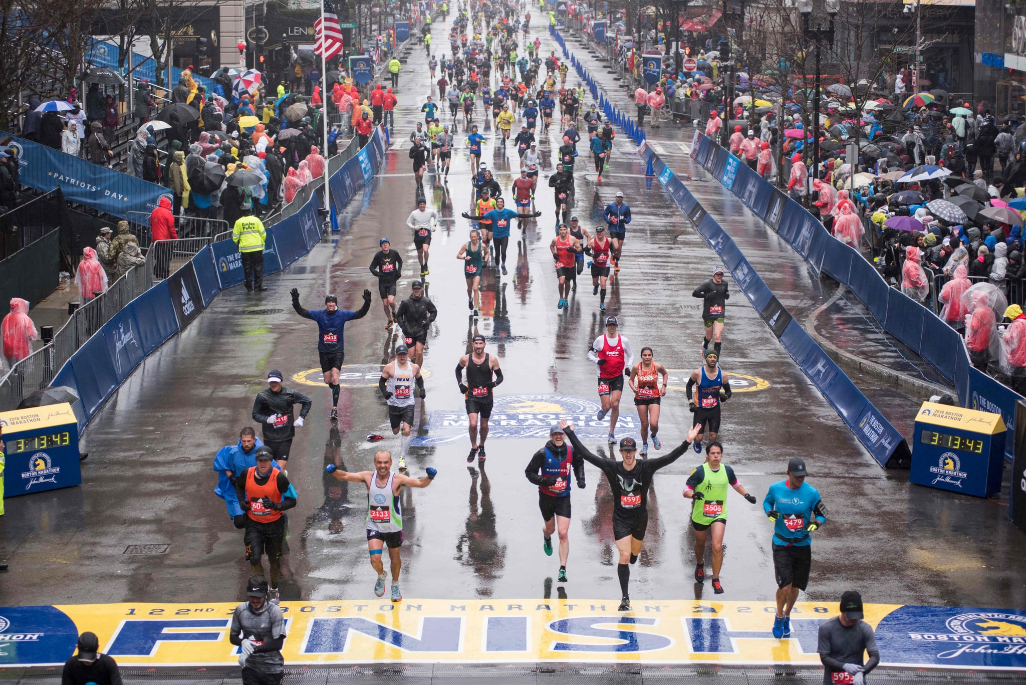 Runners come to the finish line of the 122nd Boston Marathon, where rain and high winds battered down for the duration. Monday April 16, 2018.  / AFP PHOTO / RYAN MCBRIDE        (Photo credit should read RYAN MCBRIDE/AFP/Getty Images)