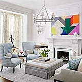 Bill and Giuliana Rancic's Chicago living room employs the color blue, their favorite, as well as a large piece of statement art. The chandelier, also a focal point, is from Circa. The rug is from Stark.