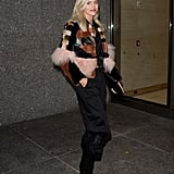 Devon Windsor wearing a patchwork jacket with black pants and ankle boots.