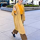 While in New York, Zoë showed us how easy it is to pair a mustard yellow sweater with a long duster and plaid pants.