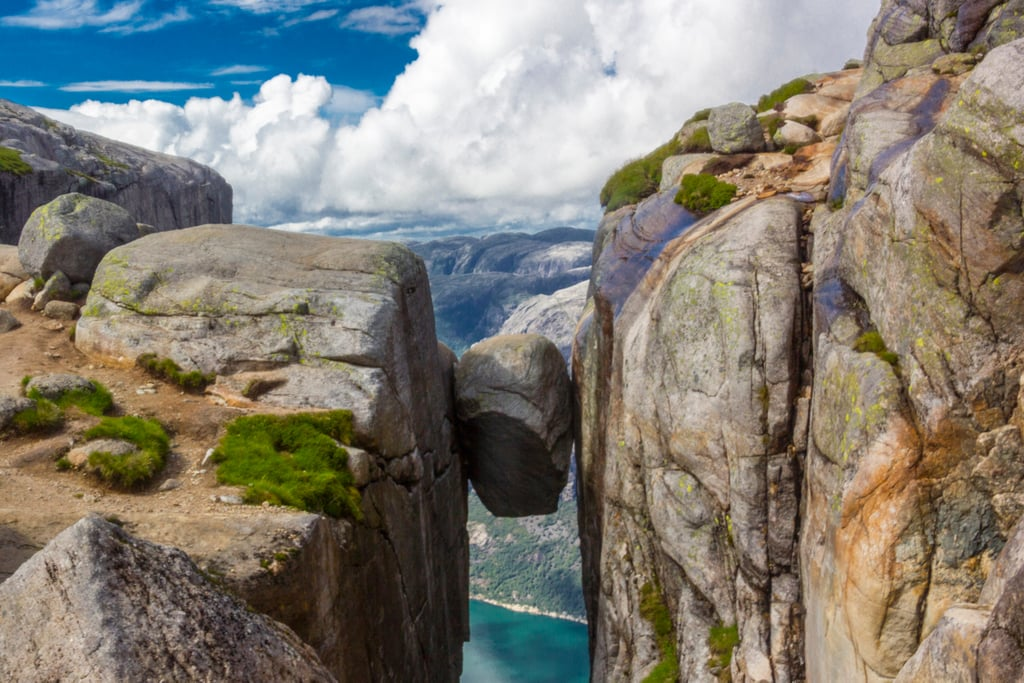 Stand on a Boulder Wedged Between Mountains at Kjeragbolten in Norway