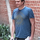 Jason Segel with two bottles of wine.