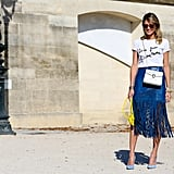 Helena Bordon paired a casual tee with a blue fringed skirt and a pop of contrasting yellow with her bag.