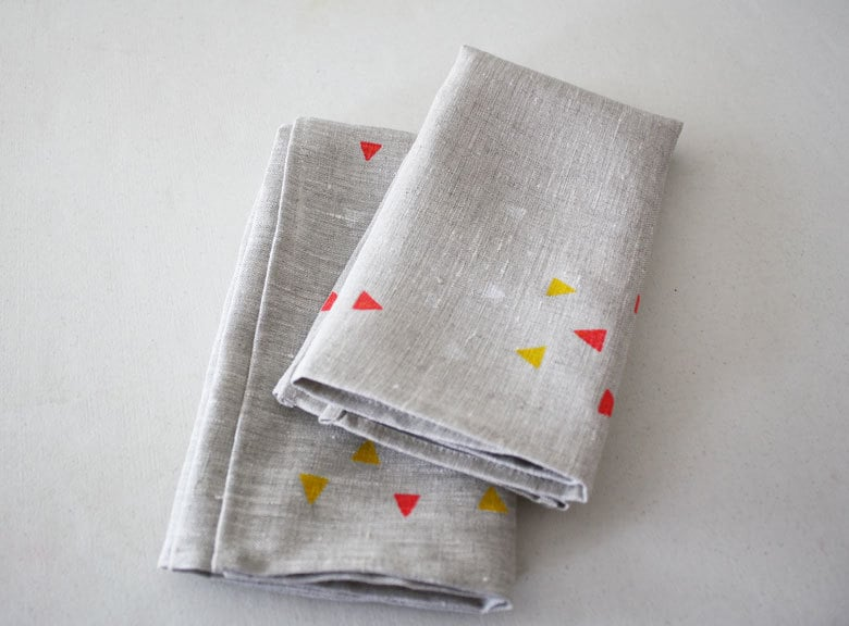 The Set of Two Geo Napkins ($28) from Linea Carta is hand-printed on linen with water-based inks in neon coral, white, and yellow.