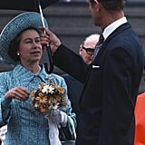Prince Philip holds an umbrella for Queen Elizabeth II in Canada in 1976