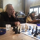 This picture shows a scene that's common in Greece: men playing chess in a coffee shop.