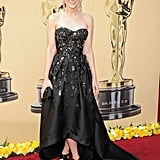 Adorned with floral crystal brooches, miscellaneous buttons, and miniature scissors, Carey's voluminous Prada dress was the talk of the 2010 Oscars.