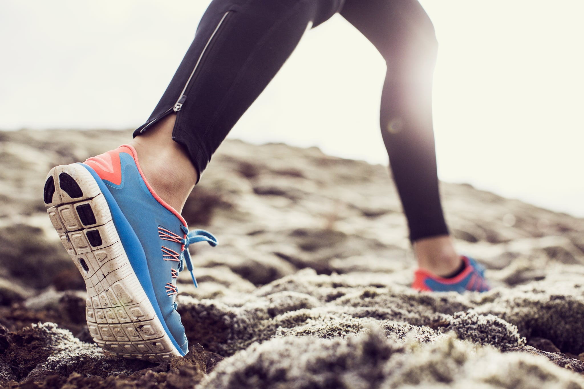 Close up, low angle shot of a female runners trainers, running through mossy terrain in Iceland. Blue trainers, black running leggings with backlit sunshine.