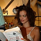 A model read a book about models — Model: The Ugly Business of Beautiful Women by Michael Gross — at Tuleh's Spring 2006 show.