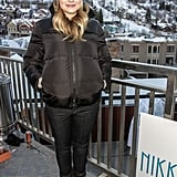 Kristen Bell bundled up in a Coach brown puffer jacket, black snow boots, Paige denim, and a Coach gray knit beanie.