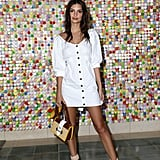 Emily Ratajkowski wearing a white LPA dress at #REVOLVEfestival and carrying a Prada straw and leather Cahier bag.