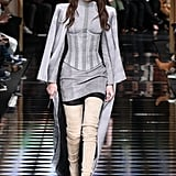 Gigi's first Balmain look was a gray suede ensemble finished with thigh-high boots and a sleek duster coat that she balanced on her shoulders.