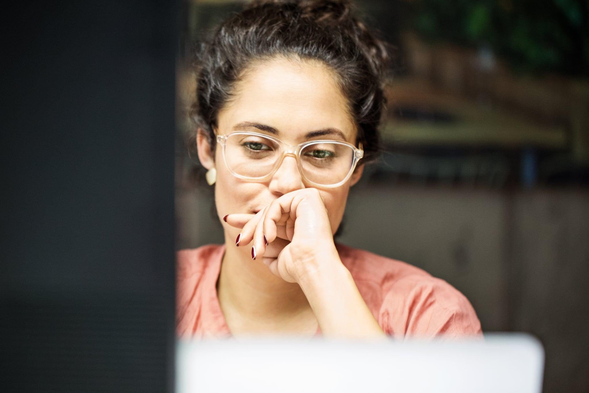Thoughtful young businesswoman using computer in office