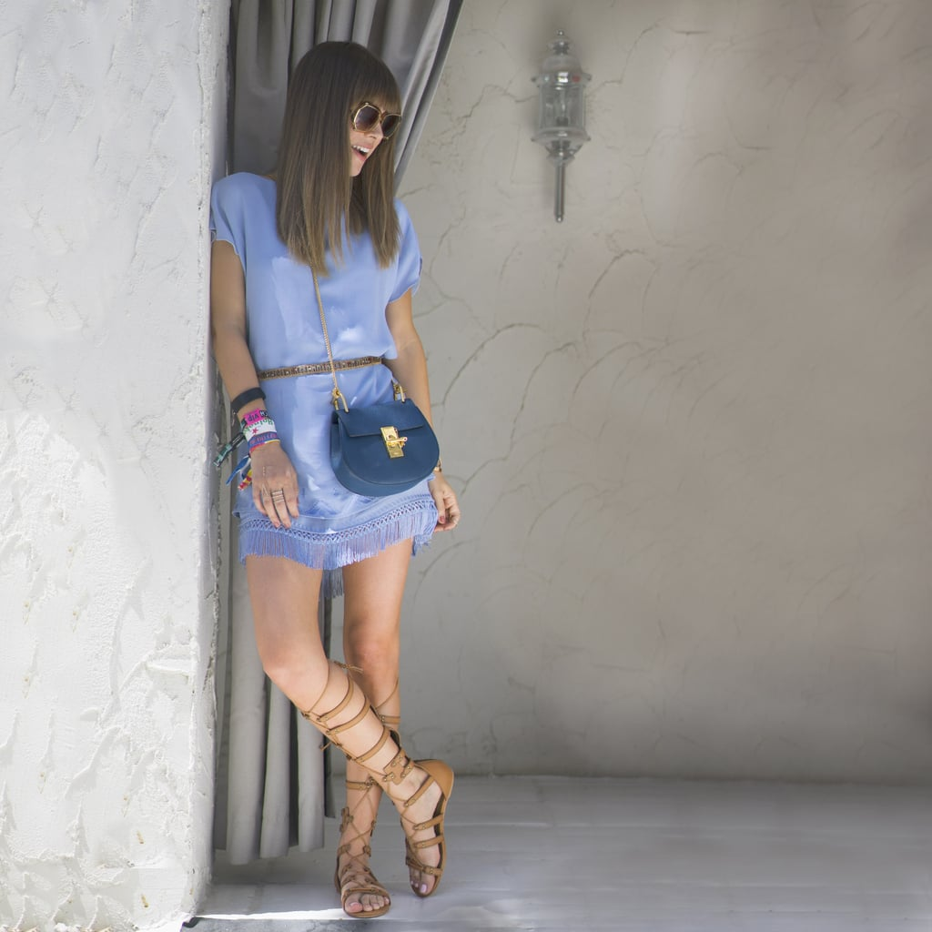 A blue dress with fringe at the hem was finished with tall, neutral gladiator sandals.