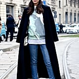 We love the glam Milan take on this jeans and sweatshirt ensemble with an elegantly draped coat and a whimsical veil fastened to her beanie.