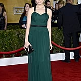 Jessica Paré looked stunning in a dark green pleated Jason Wu gown with black accents, top-notch top-knot, stunning drop earrings, and Christian Louboutin pumps.