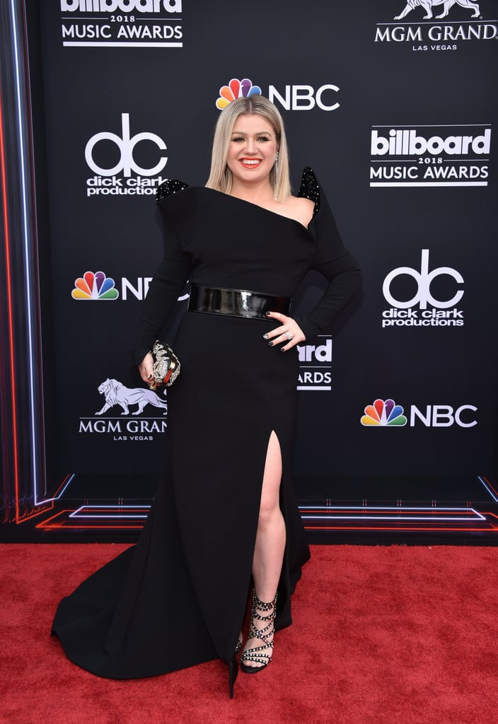 "One hot mama! Kelly Clarkson strutted her stuff on the red carpet at the 2018 Billboard Music Awards before hosting the show later in the evening. The 36-year-old singer and proud mom of two opted for a black dress sculpted with dramatic high shoulders, and all we can say is ""slay, Kelly, slay!""  ""Look at this drama!"" Kelly told E! red carpet correspondent Jason Kennedy before revealing she was rocking a Christian Siriano design. The original American Idol winner also performed during the award show ceremony and kept viewers — including Taylor Swift and former Idol judge Simon Cowell — entertained throughout the night. Keep reading to see more photos of Kelly's first time hosting the BBMAs.      Related:                                                                                                           Kelly Clarkson Opens the Billboard Music Awards With a Tearful Plea For Gun Control"