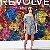 Emma Roberts wearing a gingham off-the-shoulder minidress, Salvatore Ferragamo sunglasses, and purple sandals at the Revolve Festival party.