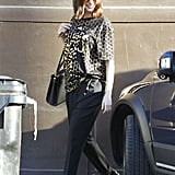 Anne completed her metallic graphic T-shirt with loose, tapered trousers, Robert Clergerie oxford flats, a pair of go-to sunglasses, and her monogrammed Valentino My Rockstud bag.
