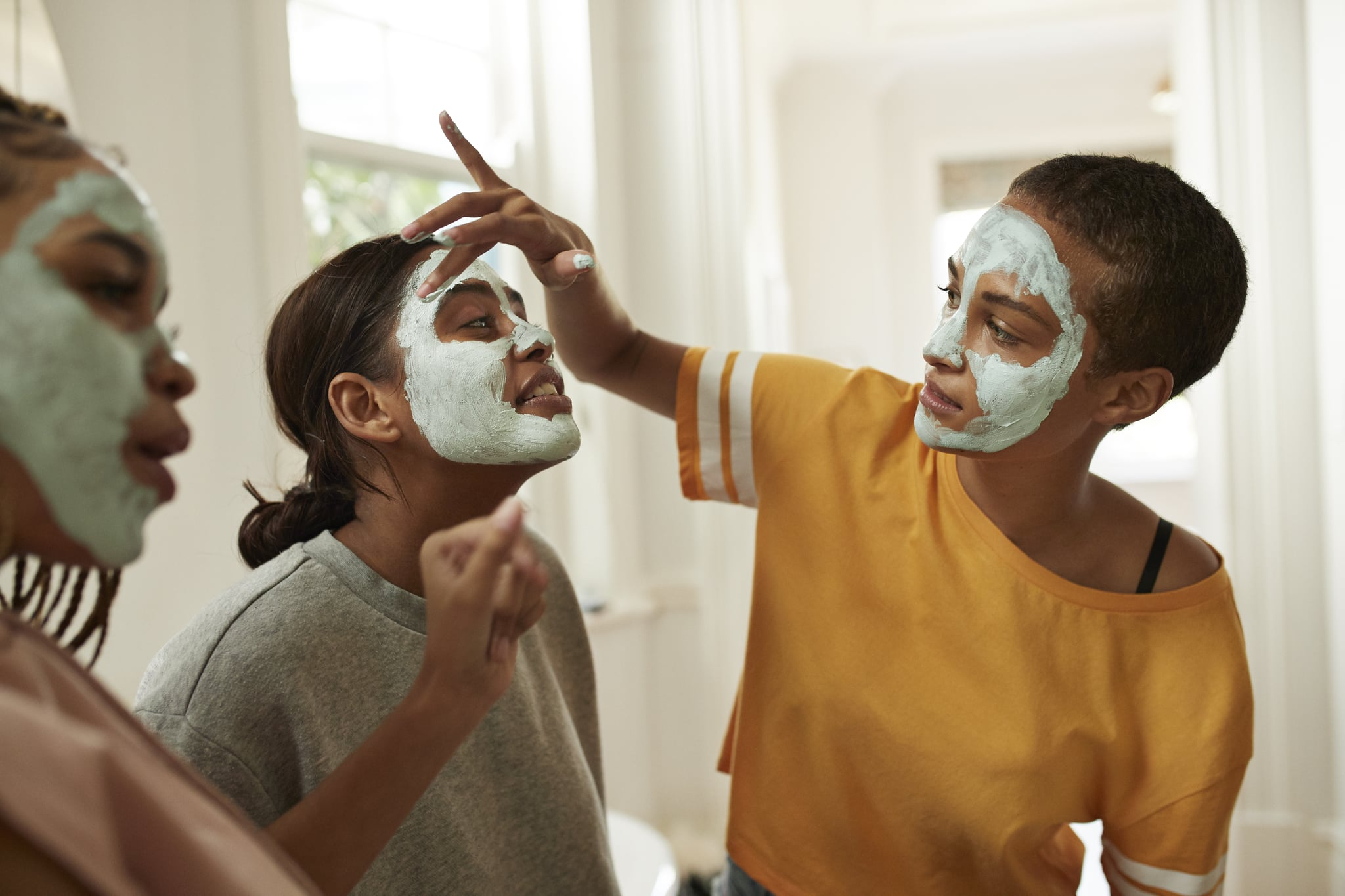 Woman looking at female friend spreading facial cream with fingers in bathroom at home