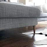After surfing the web, they found a company called Uncle Bob's Workshop that sells superaffordable legs specifically for Ikea couches. They  chose solid walnut ones for a more expensive, midcentury look.