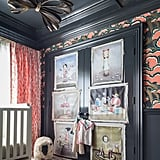 """Behind the crib is a swath of bright drapery fabric from LULU DK's new children's fabric line for Schumacher, while vintage oil portraits are tacked onto the closet door with nail heads for a more casual look. Tamara believes that kids are never too young to start appreciating art, so while the artist of these prints is unknown, she loves the """"Mark Ryden meets Tim Burton feel"""" of them. Photos courtesy of: Marco Ricca"""