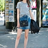 When you want a simple outfit to wear, try this combination of a gray tee, denim miniskirt, and sneakers.