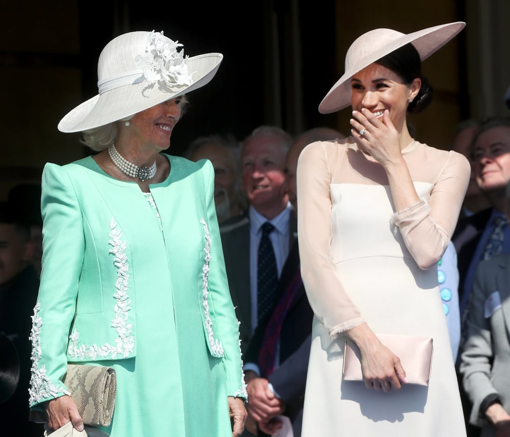 It's been all but three days since Meghan Markle and Prince Harry married in a spectacular ceremony surrounded by 600 of their closest family and friends, and it looks like the new duchess is already super close with her royal family. On Tuesday, the newlyweds made their first official appearance together as a married couple for Prince Charles's 70th birthday patronage at Buckingham Palace, and we couldn't help but notice some special moments between Meghan and mother-in-law Camilla Parker Bowles. (And by moments, we mean lots of laughs.)  Meghan and Camilla were spotted giggling and smiling during Harry's speech when a bumblebee swarmed the stage and the two couldn't hold back. We already know Camilla is a jokester based on her close, smile-filled bond with Kate Middleton, but it's great to see how she's hitting it off with Meghan. Check out all the sweet photos of Meghan and Camilla ahead, and then, read more about Prince Harry and Prince William's relationship with their stepmother.