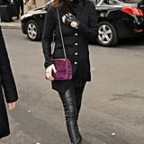 Pulling a Karl Lagerfeld with one fingerless leather glove, all-black separates, and a standout plum Chanel bag.