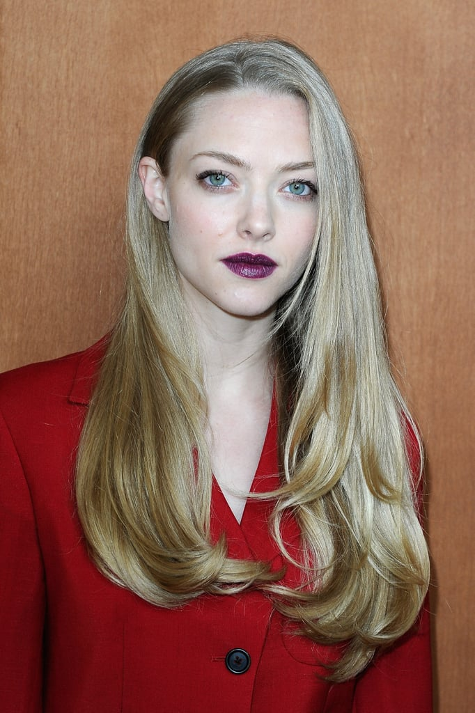 Amanda Seyfried paired dark lipstick with a bright red suit for the Miu Miu show during Paris Fashion Week.