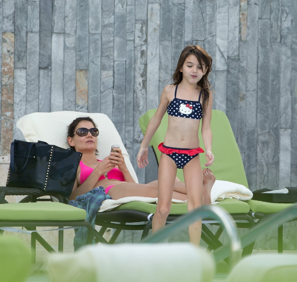 Katie Holmes and her daughter, Suri Cruise, soaked up the sun together today in Miami, Florida, where Katie showed off her bikini body by the pool. Sporting a hot-pink swimsuit, Katie was all smiles with Suri, lying out while her little one took a dip in her Hello Kitty polka-dot bikini. The look-alike pair is enjoying a relaxing end to the year following a busy couple of months. Earlier in December, Katie got into the holiday spirit with an appearance at Z100 Jingle Ball in NYC, hitting the stage to introduce Selena Gomez. During Autumn, the actress also spent time in Cape Town, South Africa, to work on the upcoming film adaptation of The Giver. Katie will play the mother of the character Jonas, opposite Alexander Skarsgard, who plays his dad, and the movie also stars Jeff Bridges, Taylor Swift, and Meryl Streep. Keep reading to see all the pictures from Katie and Suri's sweet pool date.