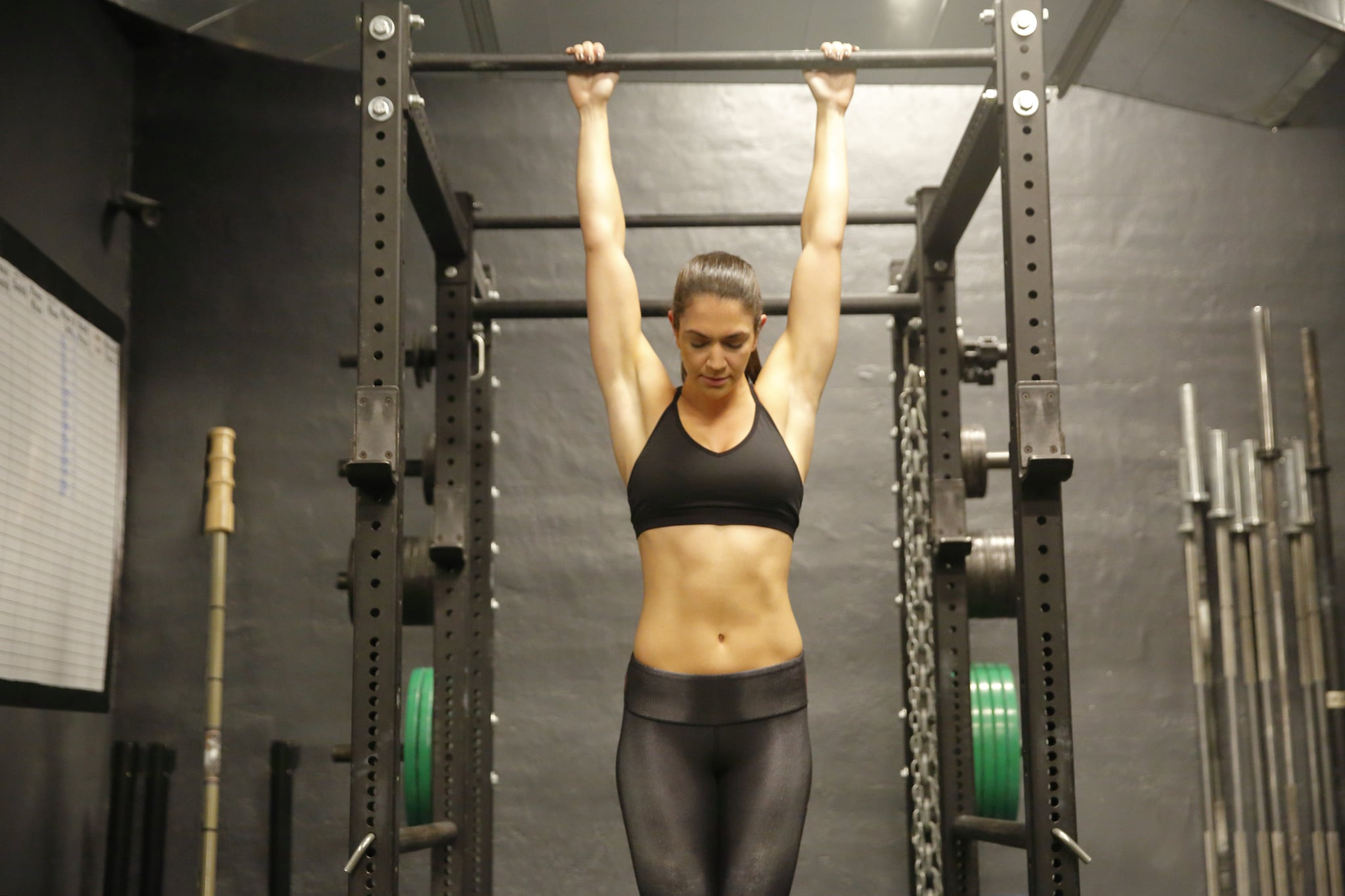 A fit, young Caucasian woman hangs from a pull up bar while doing pull ups.