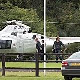 Brad Pitt carries a cup of coffee getting off the helicopter.