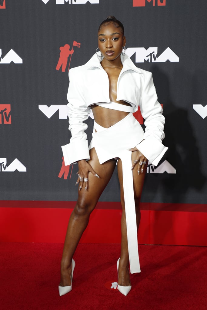 """When you're Normani, antiquated fashion rules like """"you can't wear white after Labour Day"""" are simply nonsense. On Sunday night, the singer pulled up to the MTV VMAs in a white Patrycja Pagas set and Djula jewellery looking like a million bucks. The jacket featured exaggerated cuffs, a slightly popped collar, and the perfect amount of cropped length to flaunt her abs. And the asymmetrical skirt, well, it speaks for itself. We knew there was a reason we were anxiously awaiting Normani's arrival on the red carpet, and this Patrycja Pagas set was exactly why. Her sexy red carpet outfit is just the beginning of the big night ahead. Normani is performing her hit single """"Wild Side"""" for the first time on television. She performed """"Motivation"""" at the show in 2019, and we can't wait to see what she brings out for this year's show. Check out the photos of Normani at the 2021 MTV VMAs red carpet ahead.      Related:                                                                                                           The MTV VMAs Red Carpet Is So Upbeat, the Fashion Alone Will Make You Get Up and Dance"""