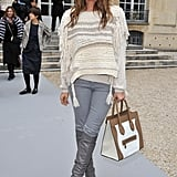Dasha Zhukova paired grey knee-high boots with matching jeans, a cosy fringed sweater, and Céline Luggage Tote bag at the Christian Dior show.