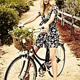 Rosie looks sweet riding her bike wearing a dress by Isabel Marant and shoes by Charlotte Olympia.