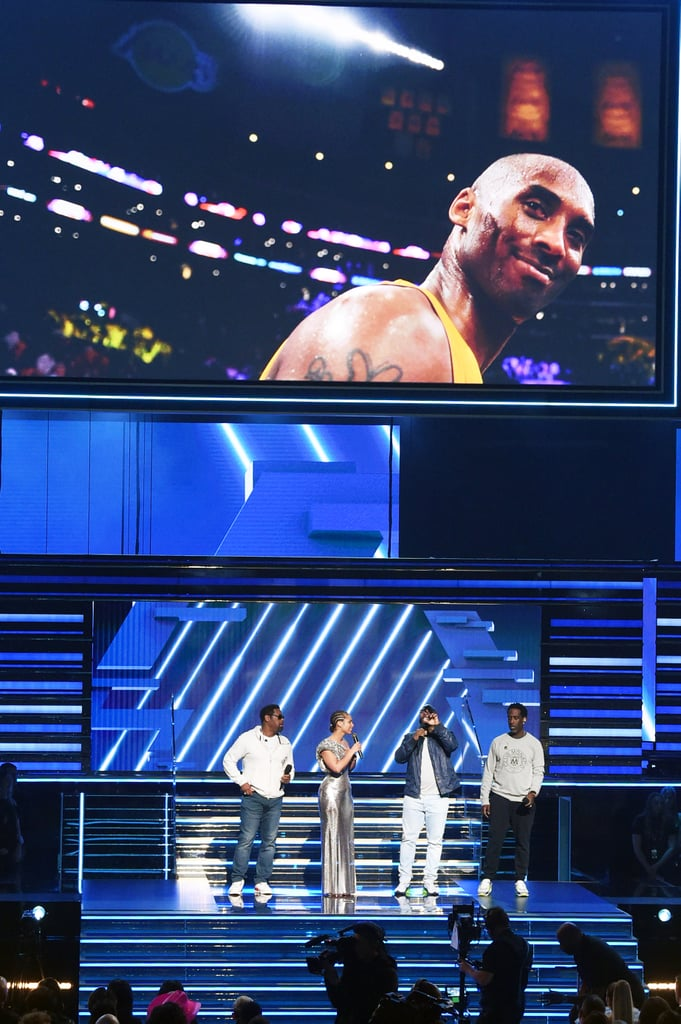 "Sunday's Grammy Awards was the biggest night in music, but it was also a night to pay tribute to some icons and legends. Following the death of Kobe Bryant earlier in the day, the Recording Academy announced a desire to include a special memorial for the recently retired Los Angeles Lakers superstar, in additional to the planned tribute for rapper Nipsey Hussle.  After a rousing performance from Lizzo, host Alicia Keys opened the ceremony with a few words on the late ball player and his daughter. ""Earlier today, Los Angeles, America, and the whole wide world lost a hero,"" she began. ""We're literally standing here, heartbroken, in the house that Kobe Bryant built."" The singer went on to ask the audience to hold Bryant, his daughter, and everyone else lost in the crash ""inside of you"" and to share their strength with their families. Keys than sang a stirring acoustic rendition of Boyz II Men's ""It's So Hard to Say Goodbye to Yesterday,"" joined by the members of the band onstage, which ended with the camera panning to both of Bryant's retired jersey numbers illuminated in the Staples Center rafters. Bryant is known worldwide for his NBA career, including winning five championships with the Los Angeles Lakers and being an 18-time NBA All-Star. The former player was traveling in his private helicopter with eight other people, including his 13-year-old daughter Gianna, when it went down in Calabasas, CA, on Sunday. He is survived by his wife, Vanessa, and their three other daughters, Natalia, 17, Bianka, 3, and Capri, who was born in June 2019.  Though the family wasn't present for the tribute and hasn't issued any public statements, Bryant's friends and fans have been sharing their sadness and tributes since the news dropped. Watch the memorial from the Grammys ahead."