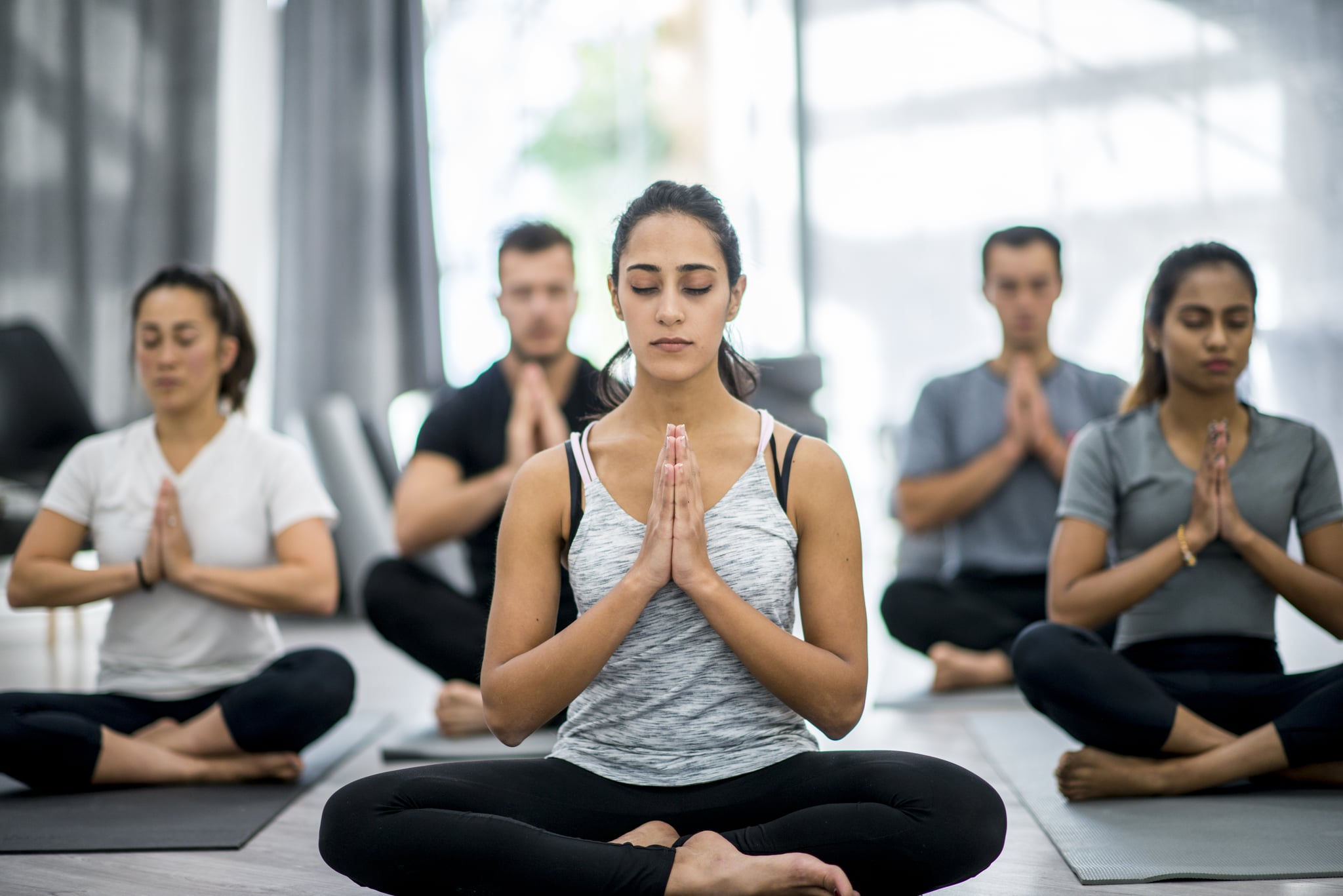 A group of adults are meditating together. They are sitting on yoga mats with their eyes closed and hands clasped together. They are in a health club.