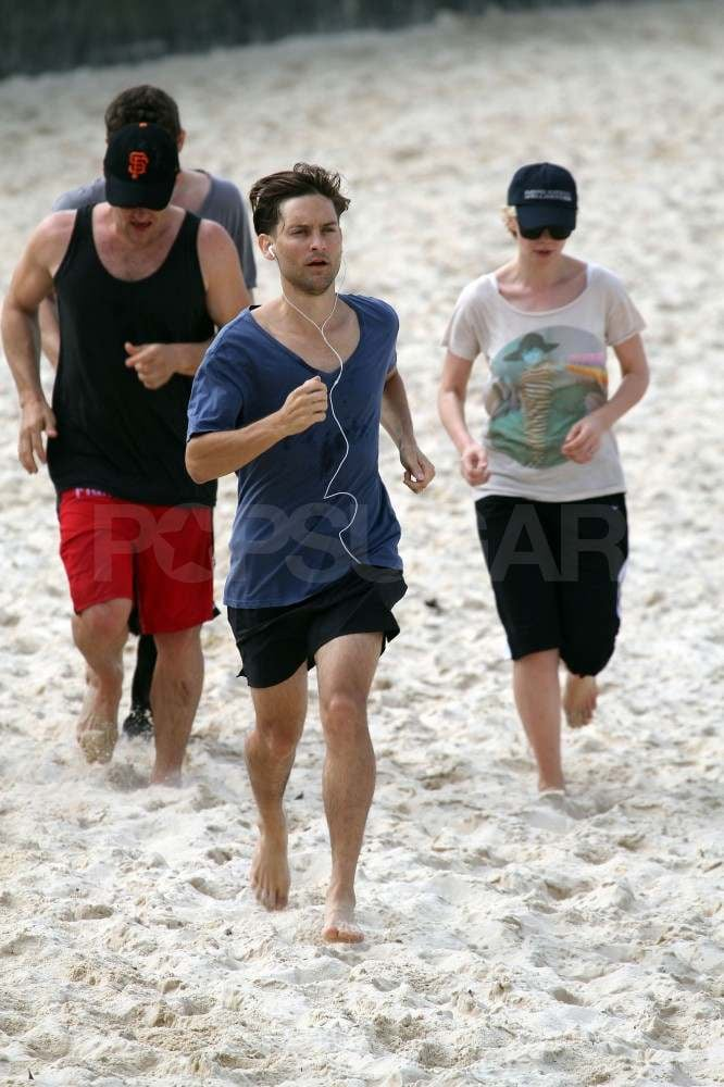 Carey Mulligan and Tobey Maguire run on the beach.