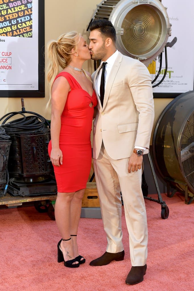 "Britney Spears and her boyfriend, Sam Asghari, have been dating for over two years now, but Monday marked the first movie premiere for the happy couple. The two traded kisses on the Once Upon a Time in Hollywood red carpet, staying close and cozy as they posed for photos. Britney wore a skintight red dress and black platform sandals, while Sam opted for a sandy-colored suit and black tie.  The darling duo first met on the set of Britney's 2016 ""Slumber Party"" music video, but they didn't make their relationship Instagram-official until New Year's Day in 2017. They frequently show off their love on social media and sparked engagement rumors early last year when Britney wore a sparkling diamond ring on that finger during a tropical getaway. Neither has confirmed this news, but judging by their red carpet PDA, these two are simply smitten with each other."
