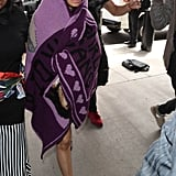 Wearing a purple blanket that actually had her name and a portrait of her face on it. She accessorized with a pair of rhinestone-encrusted Gucci sunglasses and Louis Vuitton monogrammed sandals.
